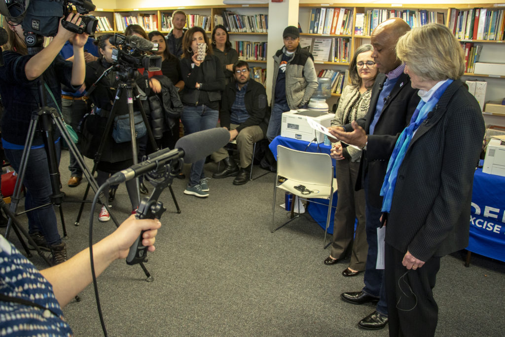 """Denver City Attorney Kristin Bronson (left to right) Mayor Michael Hancock and District Attorney Beth McCann address the press during the first clinic for the city's """"Turn Over A New Leaf"""" program to clear low-level marijuana charges. The Conflict Center, Sunnyside, Feb. 9, 2019. (Kevin J. Beaty/Denverite)"""