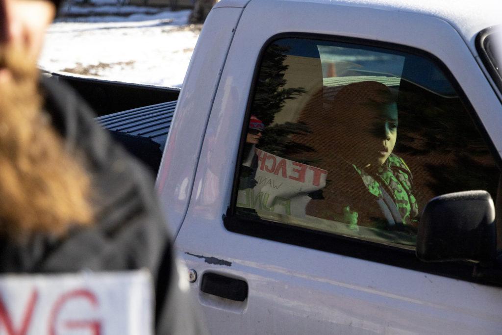 A kid watches as Kepner Beacon Middle School teachers picket outside of their school on day one of the Denver teachers' strike, Feb. 11, 2019. (Kevin J. Beaty/Denverite)