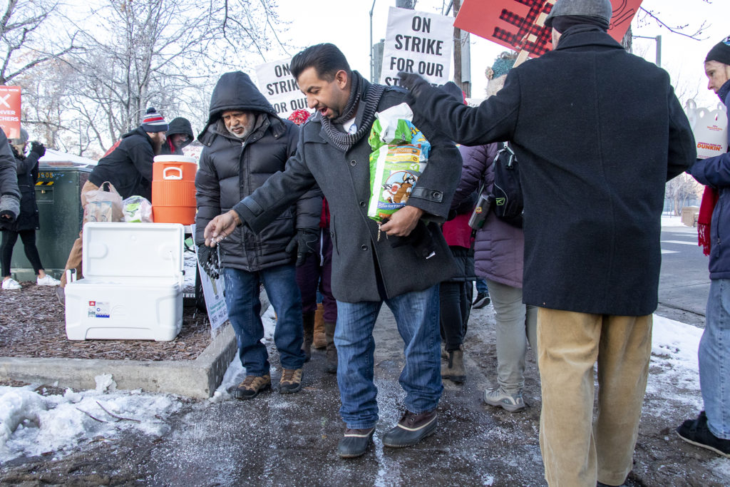 City Councilman Paul Lopez sprinkles ice-melt on an ice patch as teachers and supporters march outside of South High School on the first day of their strike, Feb. 11, 2019. (Kevin J. Beaty/Denverite)