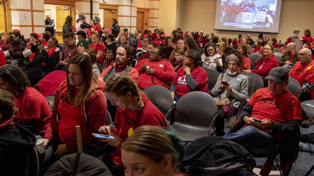 Denver teachers cheer as a live feed of a rally outside the Denver Public Library is fed inside to a negotiation room, Feb. 12, 2019. (Kevin J. Beaty/Denverite)
