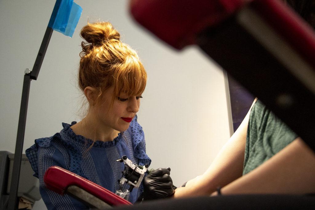Amanda Wachob tattoos Laura Reiter at the Museum of Contemporary Art, Feb. 15, 2019. (Kevin J. Beaty/Denverite)