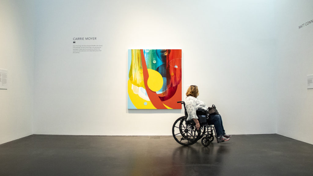 Corinne Hobbs inspects art in a Georgia O'Keefe exhibit at the Museum of Contemporary Art, Feb. 15, 2019. (Kevin J. Beaty/Denverite)