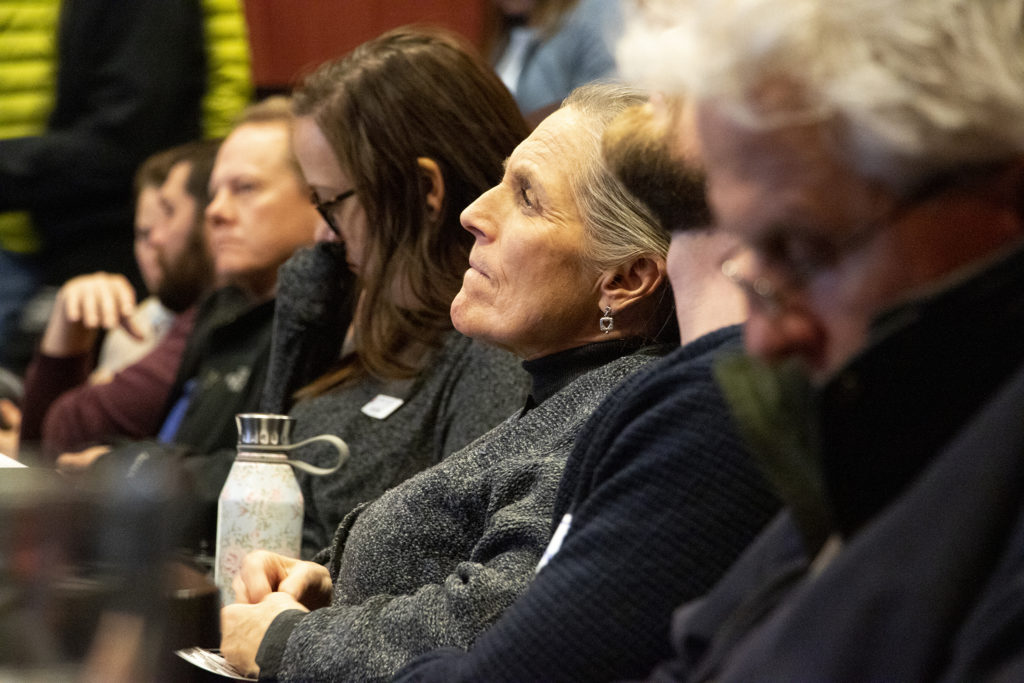 """Jeanne Granville listens in the audience as the West Colfax BID holds a meeting on possible outcomes for the """"Colfax Clover"""" project, Feb. 26, 2019. (Kevin J. Beaty/Denverite)"""