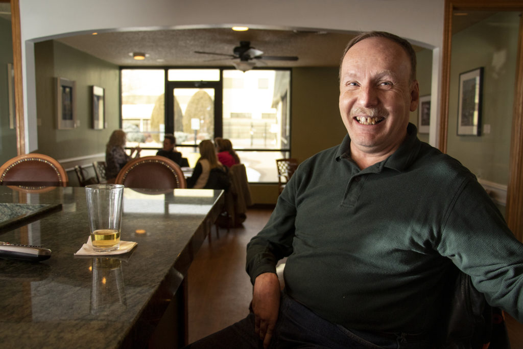 Phil Wampler, who has lived in Windsor Gardens for two and a half years, poses for a portrait at the Blossoms Restaurant bar in the neighborhood's community center. Feb. 27, 2019. (Kevin J. Beaty/Denverite)