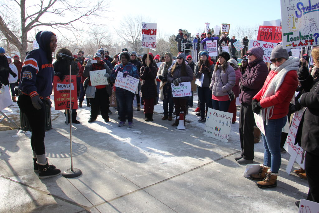 Dr. Senella Baldwin (left), a school psychologist at Legacy Options High School, speaks during a rally supporting teachers during the strike on Monday, Feb. 11, 2019, at Montbello Central Park. (Esteban L. Hernandez/Denverite)
