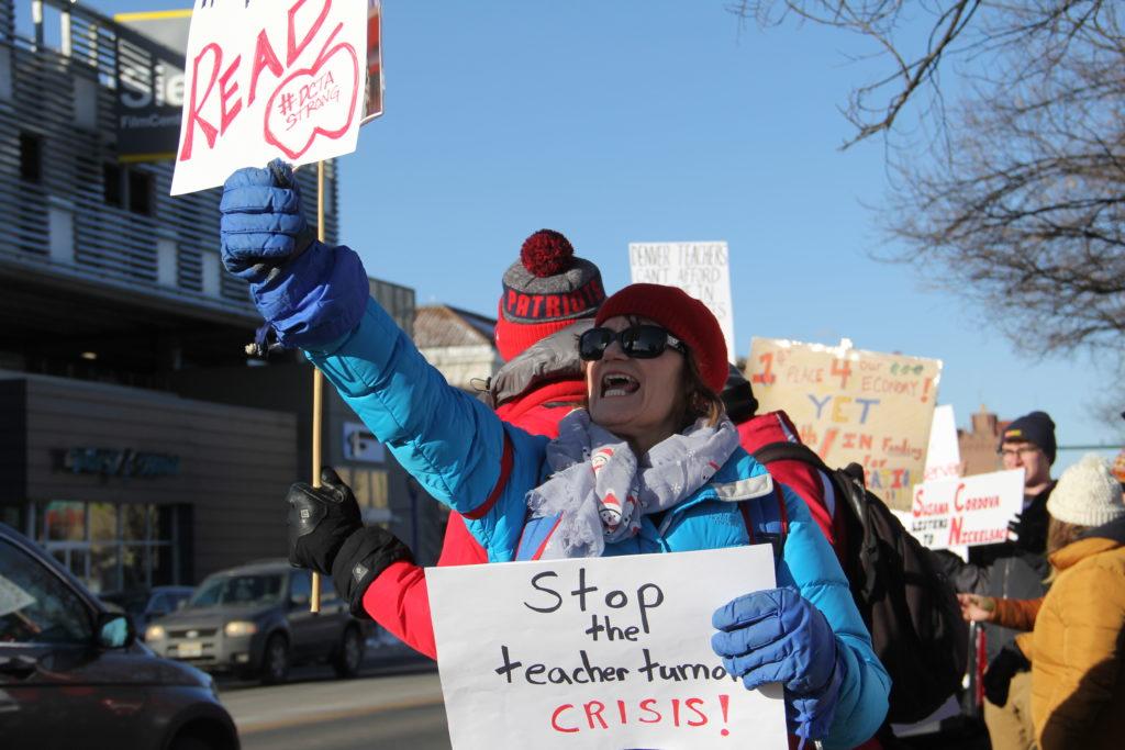 East High School teacher Pam Gamble  holds up signs on Colfax Avenue during the second day of the Denver teacher strike on Tuesday, Feb. 12, 2019, in Denver. (Esteban L. Hernandez/Denverite)