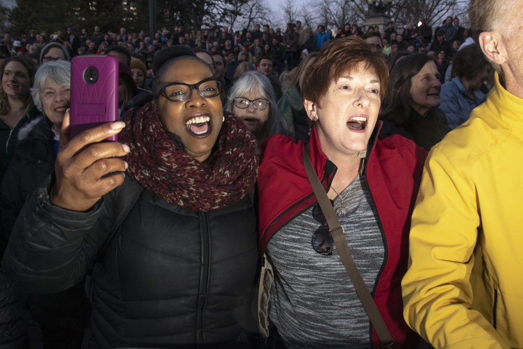 Sandra Lofton (left) and Mary Dexter sing in an embrace before presidential candidate John Hickenlooper takes the stage rally at Civic Center Park, March 7, 2019. (Kevin J. Beaty/Denverite)