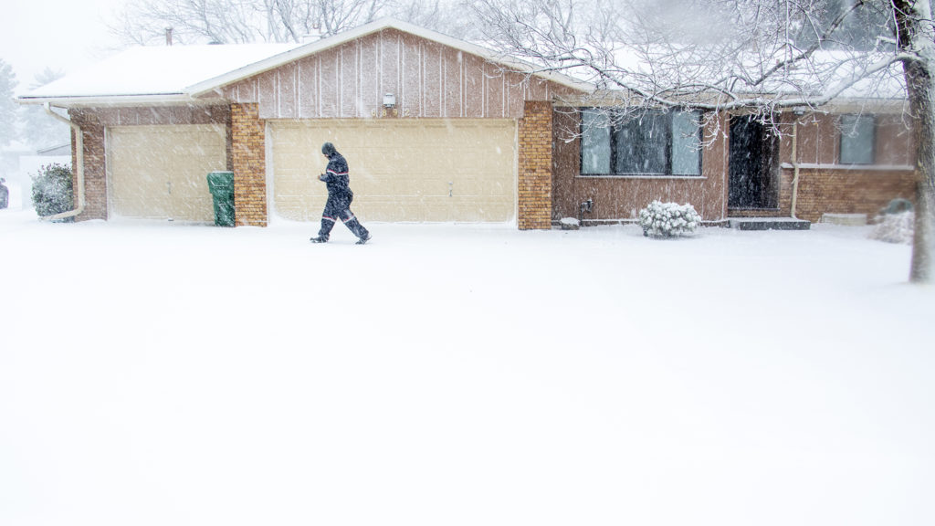 "Luis Sanchez walks part of his daily route in Denver's Goldsmith neighborhood during a ""bomb cyclone"" blizzard, March 13, 2019. (Kevin J. Beaty/Denverite)"