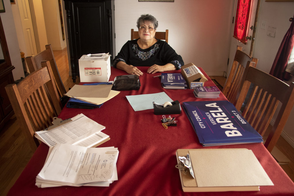 Veronica Barela poses for a portrait amid campaign materials in her Barnum West home, March 14, 2019. (Kevin J. Beaty/Denverite)