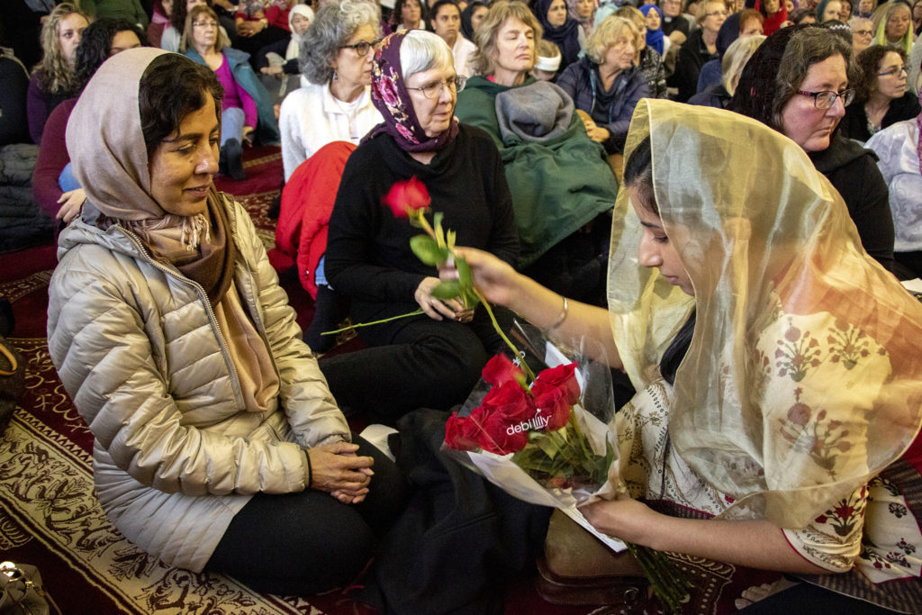 Naureen Singh, policy director with Colorado Sikhs, hands a rose to Gazala Hays during a vigil for the victims of a massacre at a Christchurch, New Zealand, mosque at the Colorado Muslim Society, March 16, 2019. (Kevin J. Beaty/Denverite)