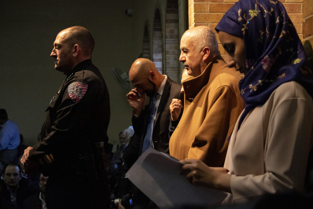 Arapahoe County Sheriff Tyler Brown (left) listens during a vigil for the victims of a massacre at a Christchurch, New Zealand, mosque at the Colorado Muslim Society, March 16, 2019. (Kevin J. Beaty/Denverite)