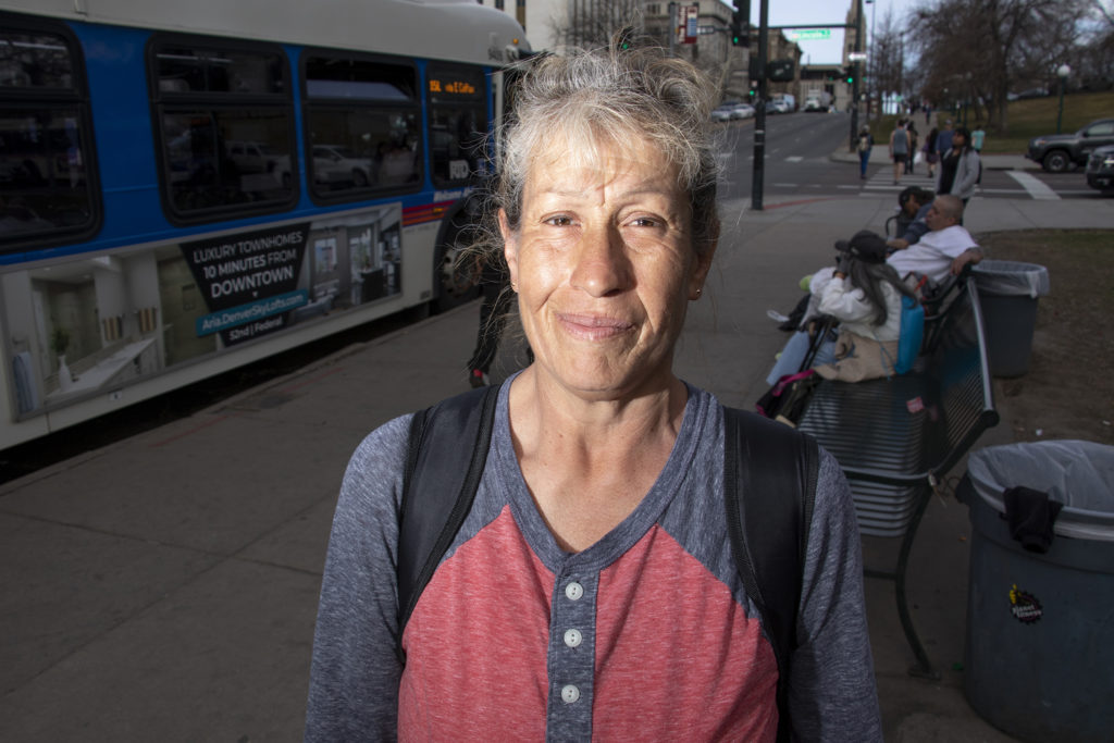 Belinda Schutter poses for a portrait at the RTD bus stop on Colfax Avenue at Broadway, March 28, 2019. (Kevin J. Beaty/Denverite)
