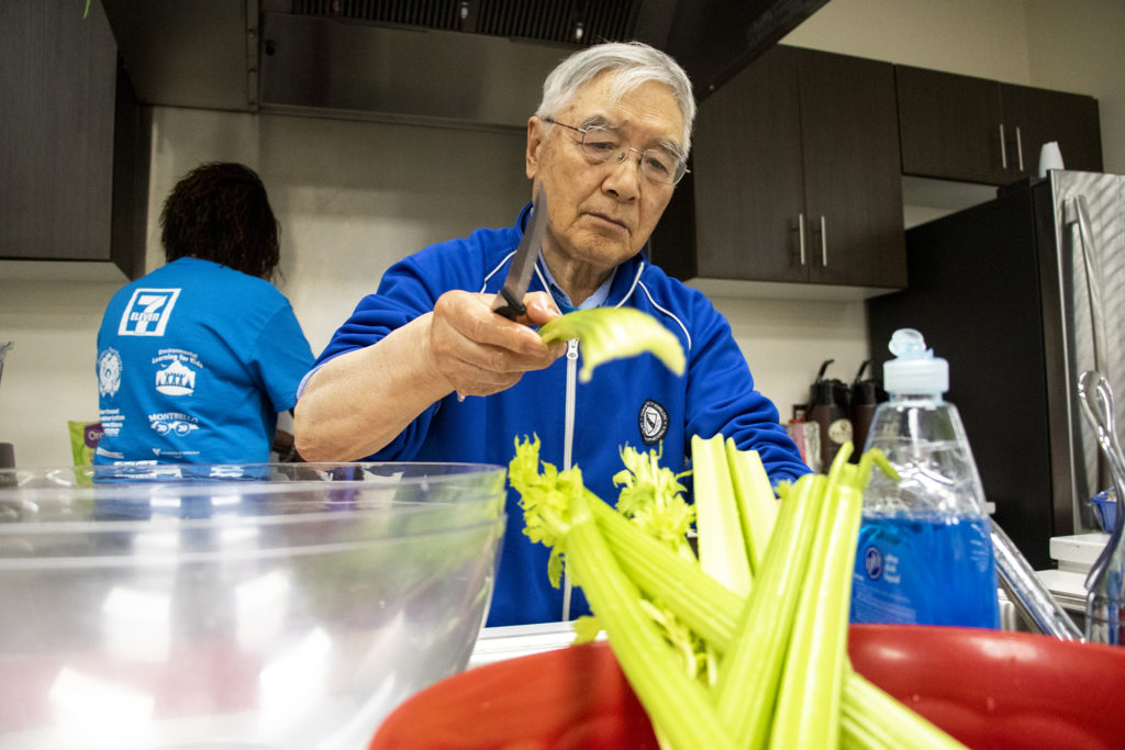 Fande Li slices celery during a healthy cooking class in the Montbello community room in the neighborhood's Save A Lot food store, March 28, 2019. (Kevin J. Beaty/Denverite)