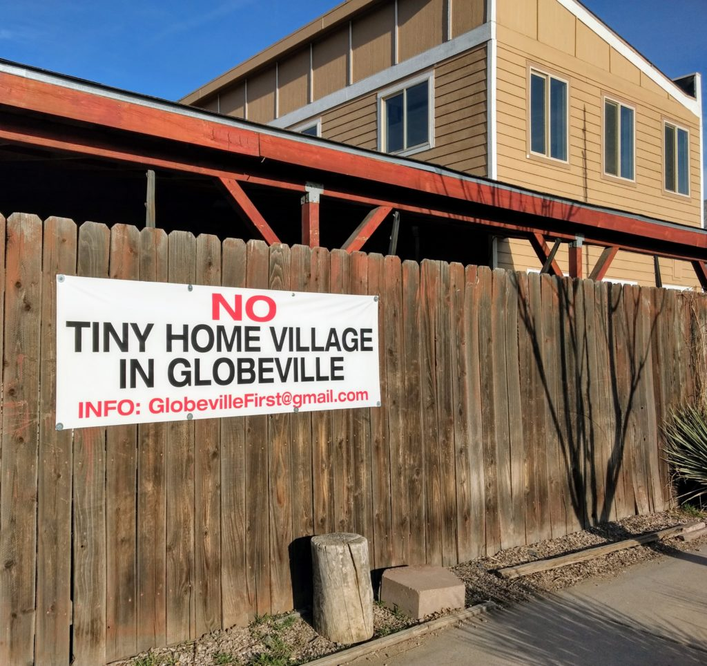 A banner a new Globeville group put up across the street from the site the city has proposed as the new home for tiny homes for the homeless. March 28, 2019. (Donna Bryson/Denverite)