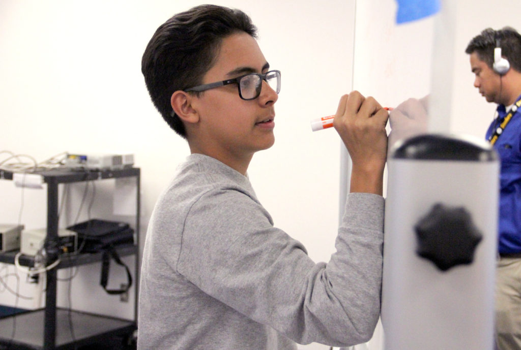 Emilio Carrasco, 14, writes on a whiteboard during a SOMOS1 meeting on Wednesday, March 20, 2019, at Skinner Middle School in Denver. (Esteban L. Hernandez/Denverite)