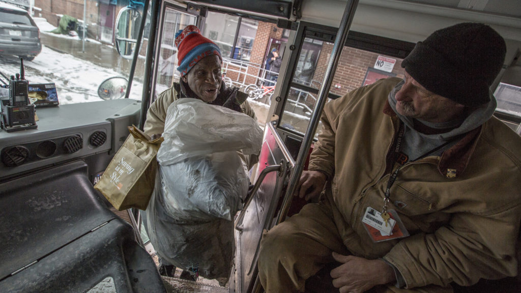 Men board a bus headed from Lawrence Street to a Denver Rescue Mission shelter in north Denver on March 13. (Hart Van Denburg/CPR News)