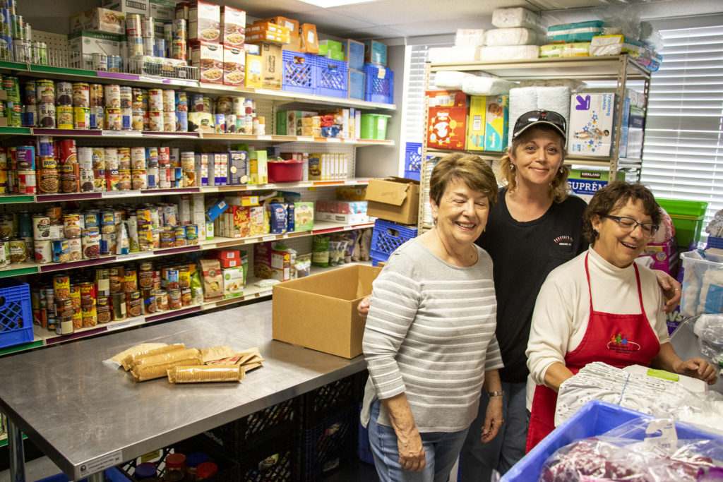 Marie hyland (left to right), Teresa Rossi and Bev Bishop pose for a portrait inside Growing Home's Westminster food pantry, April 3, 2019. (Kevin J. Beaty/Denverite)