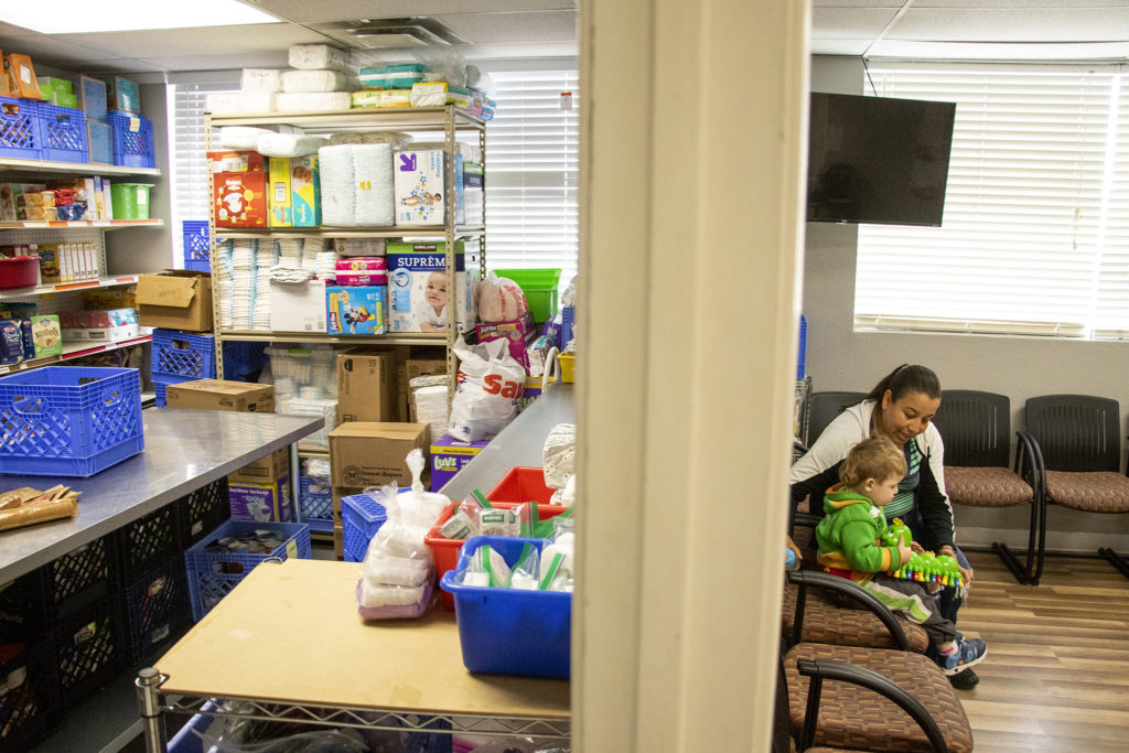 Angelica Venegas watches over a kid inside Growing Home's food pantry in Westminster, April 3, 2019. (Kevin J. Beaty/Denverite)