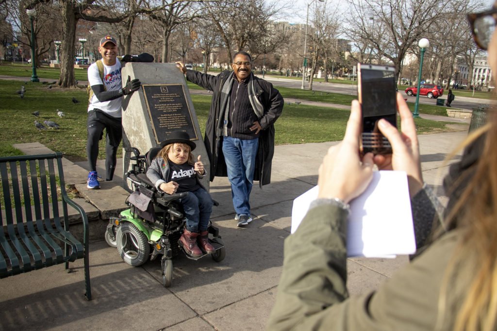"""Bicycle Colorado's Mo McCanna takes a photo of District 9 candidate Jonathan Woodley and mayoral candidates Kayln Rose Heffernan and Pendfield Tate at the """"Gang of 19"""" memorial on Colfax Avenue. Denver Streets Partnership's Amazing Denver Mobility Race, April 4, 2019. (Kevin J. Beaty/Denverite)"""
