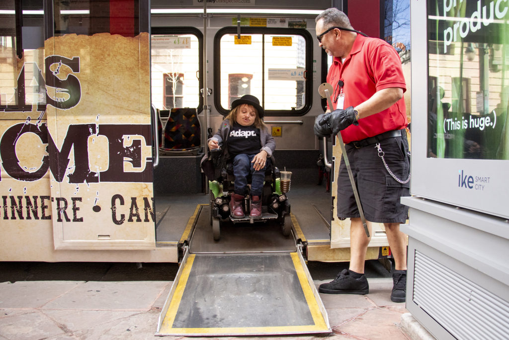 Ian Trujillo helps mayoral candidate Kayln Rose Heffernan off his 16th Street Mallride during the Denver Streets Partnership's Amazing Denver Mobility Race, April 4, 2019. (Kevin J. Beaty/Denverite)