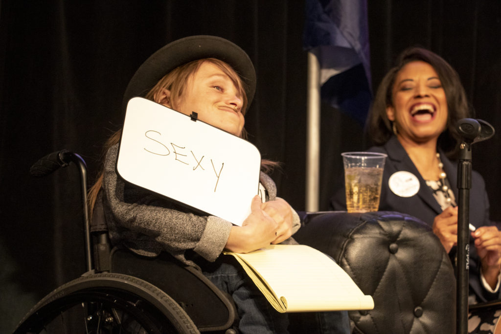 Kalyn Rose Heffernan holds up the one word she'd use to pitch herself as mayor. A mayoral candidate forum on LGBTQ issues at the Exdo event center, RiNo, Five Points, April 4, 2019. (Kevin J. Beaty/Denverite)