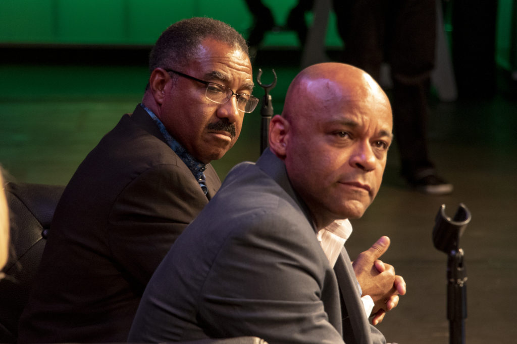 Penfield Tate (left) and Mayor Michael Hancock sit on a mayoral candidate forum about LGBTQ issues at the Exdo event center, RiNo, Five Points, April 4, 2019. (Kevin J. Beaty/Denverite)