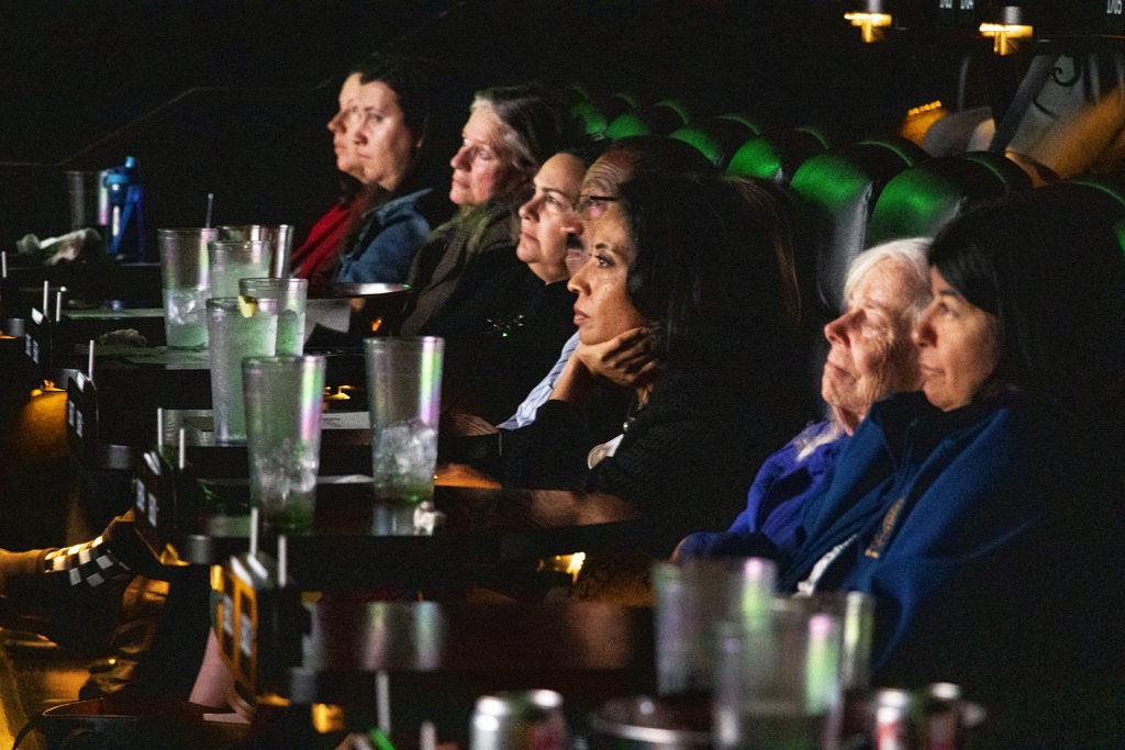 """Mayoral candidate Lisa Calderón watches """"Owned"""" during a GoodCinema screening and housing forum at Alamo Drafthouse Sloans Lake, April 16, 2019. (Kevin J. Beaty/Denverite)"""