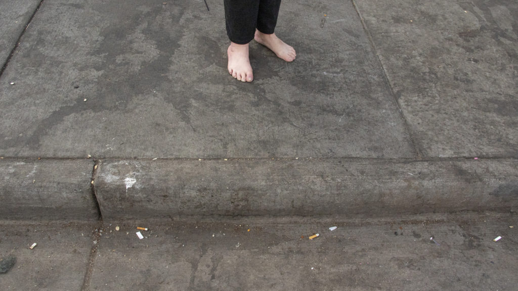 A woman stands barefoot outside of the Denver Rescue Mission, April 17, 2019. (Kevin J. Beaty/Denverite)