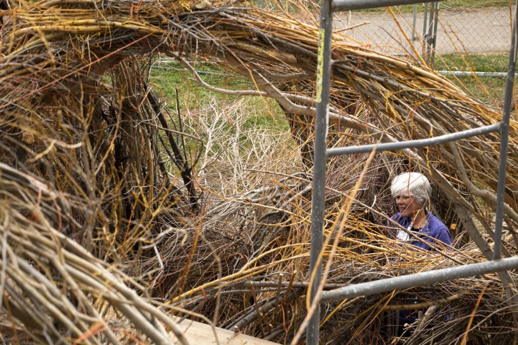 "Volunteer Demry Frankenheimer helps assemble Patrick Dougherty's ""Stickwork"" installation at the Denver Botanic Gardens' Chatfield Farms, April 18, 2019. (Kevin J. Beaty/Denverite)"