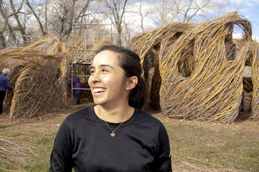 """Grace Rodriguez, assistant manager of exhibitions, art collections and registration, poses for a portrait. Patrick Dougherty's """"Stickwork"""" at the Denver Botanic Gardens' Chatfield Farms, April 18, 2019. (Kevin J. Beaty/Denverite)"""