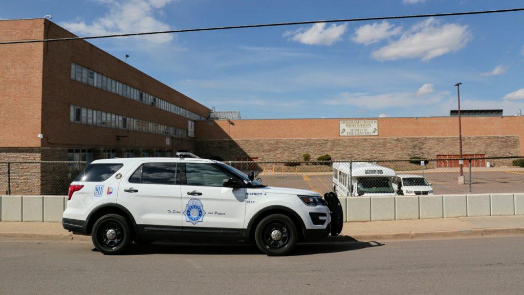 A Denver police officer parked outside of Lincoln High School on Wednesday, April 17, 2019. (Kevin J. Beaty/Denverite)