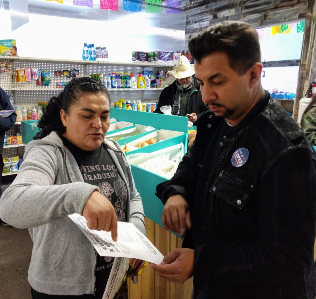 Inda Vergara, a member of the board of the Westwood co-op and a community navigator for Re:Vision goes over a co-op membership form with City Councilman Paul López on April 13, 2019. (Donna Bryson/Denverite)
