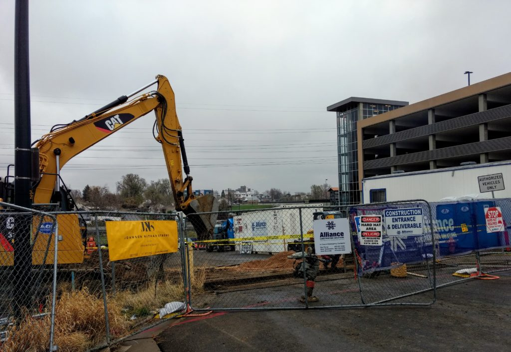 Construction under way Monday, April 22, 2019 at  5330 W. 11th Avenue in Denver, site of Sheridan Station Apartments apartments earmarked for people earning no more than 60 percent AMI. The RTD parking garage at the Sheridan rail station is in the background. (Donna Bryson/Denverite)