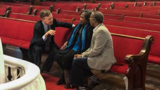 John Hickenlooper meets Polly Sheppard and the Rev. Anthony Thompson at the Emmanuel African Methodist Episcopal Church in Charleston, S.C., on Saturday, April 6, 2019. Thompson's wife was one of nine people killed by a white supremacist in a 2015 shooting at the church. Sheppard was in the church during the attack but survived. (Anthony Cotton/CPR News)