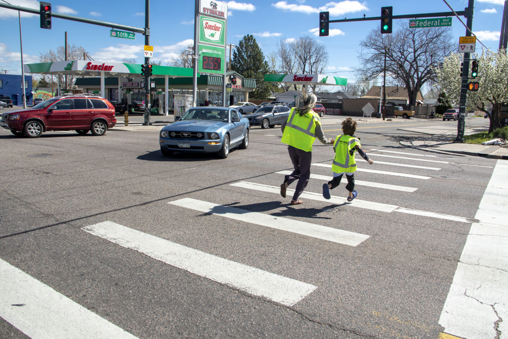 Lindsey Rosendahal and her son, Anders, runs across Federal Boulevard during a traffic slowing demo put on by Vision Zero and WalkDenver in Denver's Regis neighborhood, April 27, 2019. (Kevin J. Beaty/Denverite)