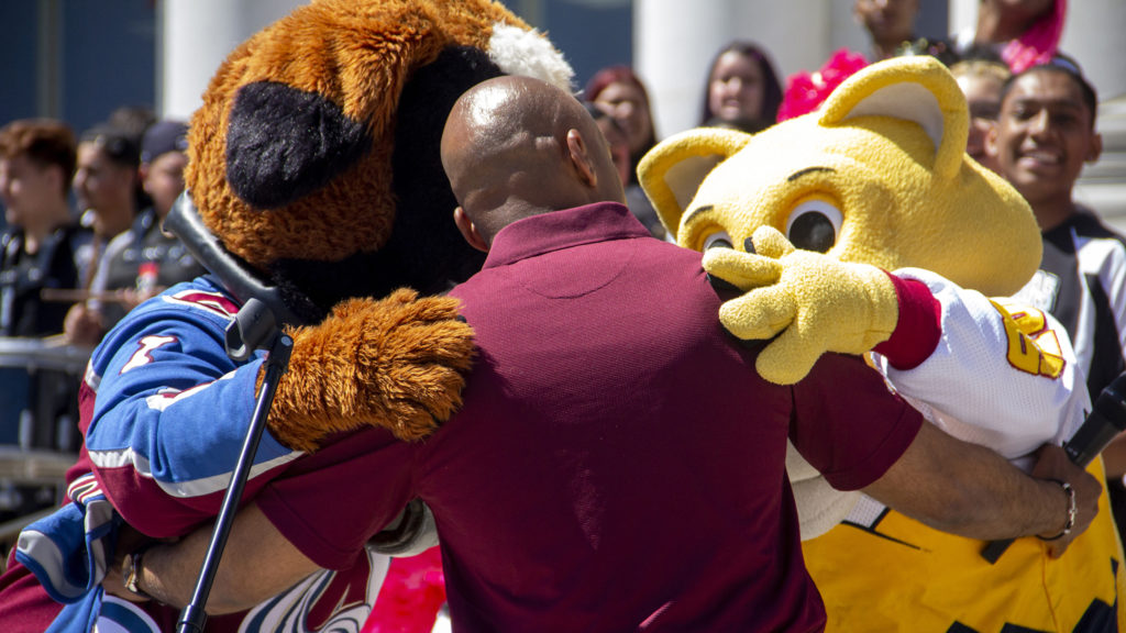 Bernie, left, Mayor Michael Hancock, center, and Rocky embrace one another at a media event announcing a tentative contract renewal that will keep the Avalanche and Nuggets in Denver for 20 more years, May 2, 2019. (Esteban L. Hernandez/Denverite)