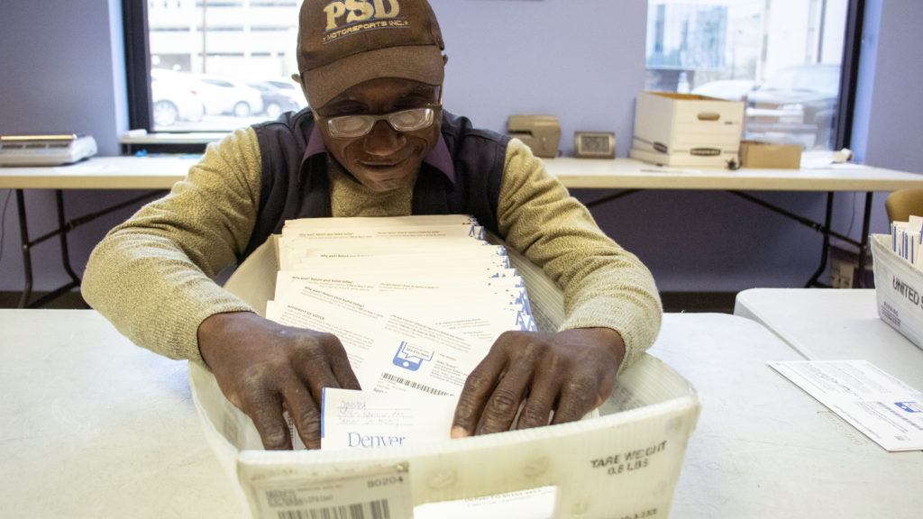 """Miguel """"Angel"""" Harlston processes ballots inside Denver Elections Division headquarters on election day, May 7, 2019. (Kevin J. Beaty/Denverite)"""
