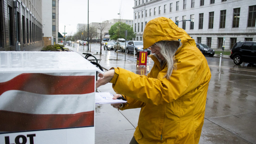 Cheryl Specter drops not one, but three ballots outside of the Denver Elections Division on election day, May 7, 2019. (Kevin J. Beaty/Denverite)