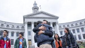 Kevin Matthews hugs David Champion at a pro-Initiative 301 press conference, May 9, 2019. (Kevin J. Beaty/Denverite)