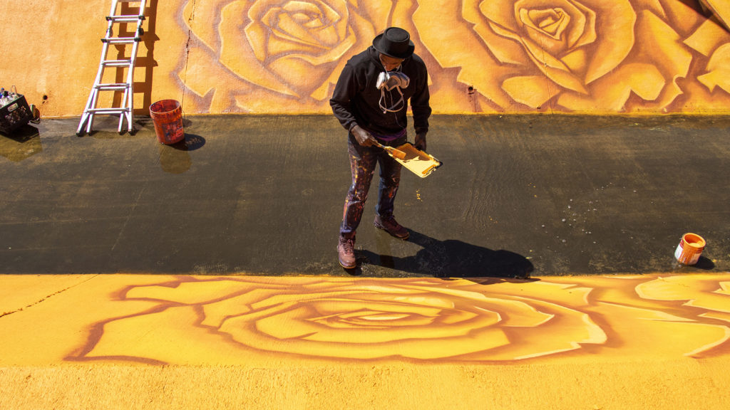 Thomas Evans, AKA Detour, paints a mural in a drainage channel running through Montbello, May 11, 2019. (Kevin J. Beaty/Denverite)