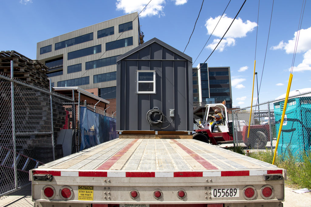 A tiny home is moved from the Beloved Community Village's second home in Five Points, May 13, 2019. (Kevin J. Beaty/Denverite)