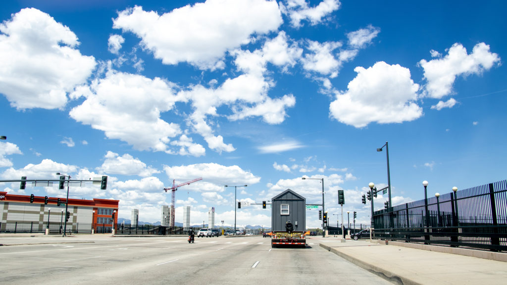 Tiny homes from the Beloved Community Village's second home in Five Points cruise through Denver on their way to Globeville, May 13, 2019. (Kevin J. Beaty/Denverite)