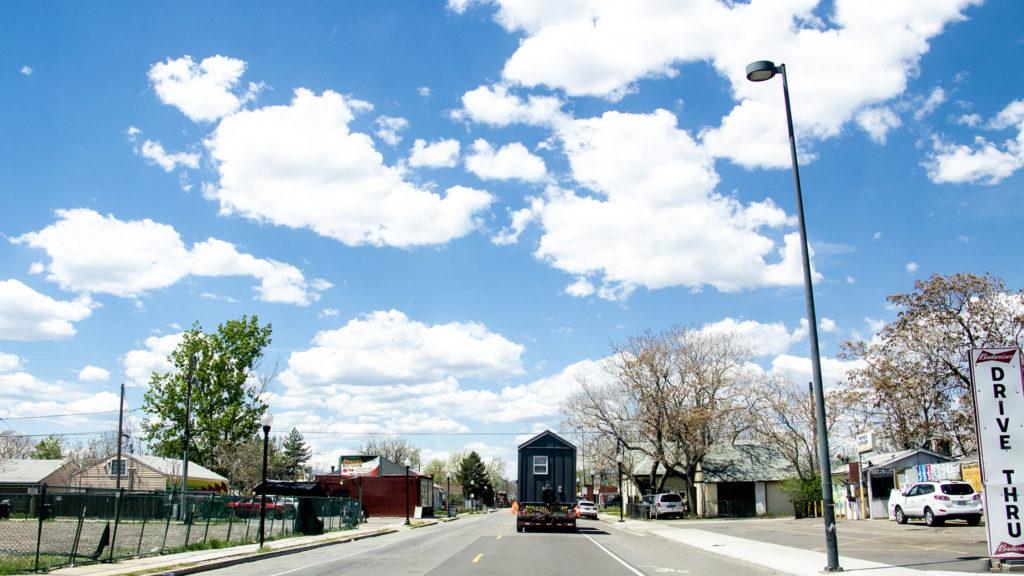 Tiny homes from the Beloved Community Village's second home in Five Points are carried through Globeville, May 13, 2019. (Kevin J. Beaty/Denverite)