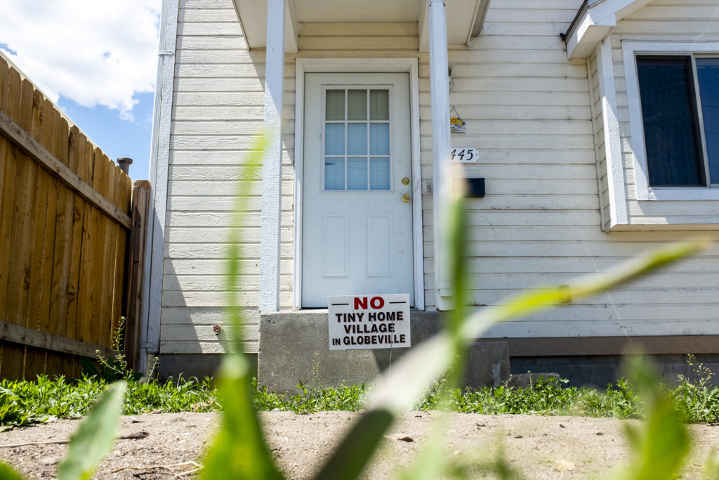 """A home across the street from the Beloved Community Village's new Globeville Home reads """"NO TINY HOME VILLAGE IN GLOBEVILLE,"""" May 13, 2019. (Kevin J. Beaty/Denverite)"""