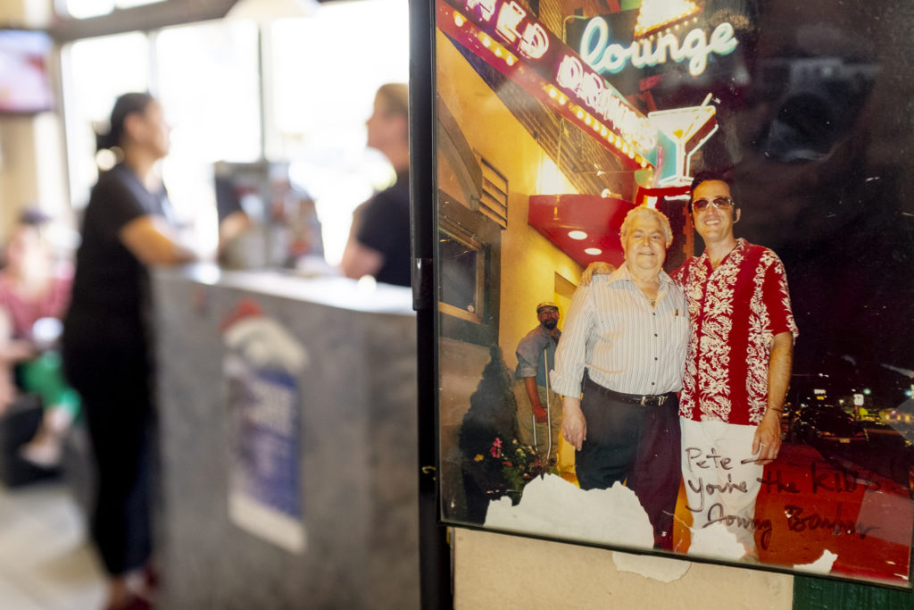 A portrait of Pete Contos and Jonny Barber on Colfax hangs inside Pete's Kitchen, May 13, 2019. (Kevin J. Beaty/Denverite)