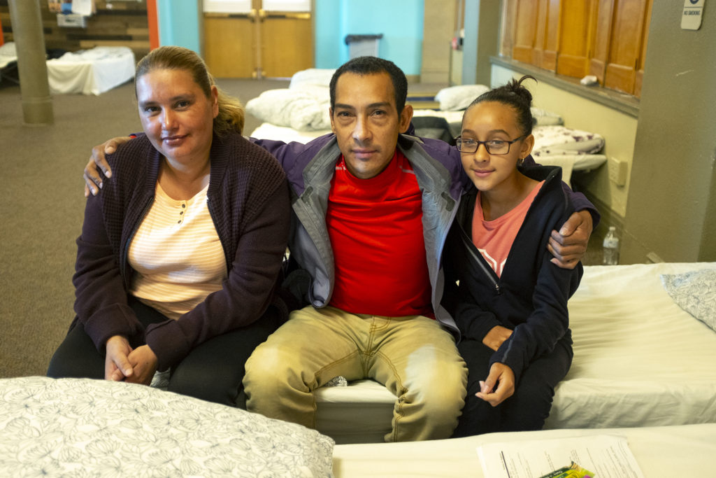 Victor Inestroza poses for a portrait with Maria Jeanette (left) and his daughter, Marta, on a cot in Denver Community Church of Christ's basement, May 14, 2019. (Kevin J. Beaty/Denverite)