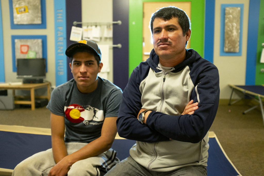 Anibal Lopez poses for a portrait with his son, Jorde, on a cot in Denver Community Church of Christ's basement, May 14, 2019. (Kevin J. Beaty/Denverite)