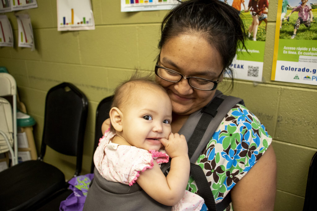 Ivana Mendez poses for a portrait with her daughter, Arabella, inside Inner City Parish's food pantry. La Alma-Lincoln Park, May 15, 2019. (Kevin J. Beaty/Denverite)