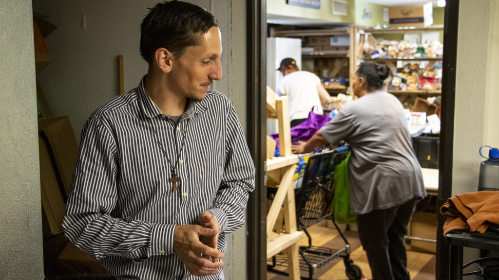Michael Bruno, who runs Inner City Parish's food pantry, speaks to a reporter in a stockroom. La Alma-Lincoln Park, May 15, 2019. (Kevin J. Beaty/Denverite)
