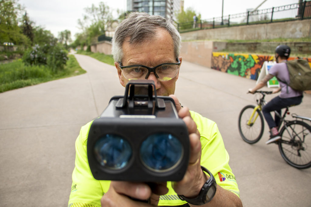 Denver Parks and Recreation park ranger Eric Knopinski checks cyclists' speeds on the Cherry Creek Trail, May 16, 2019. (Kevin J. Beaty/Denverite)